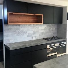 Black is back!  This stunning kitchen design by @cube_cabinets features Thermolaminated Tempest Woodgrain doors and panels which have been beautifully complimented by the timber shelves and concrete benchtops.  #polytec #vinyl wrap #kitcheninspo #interiordesign #interiorstyling #design #homedecor #homeinspo #designinspo #interiors #blackisback