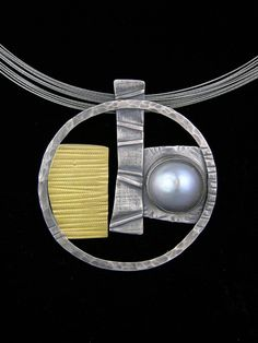"Elaine Rader Jewelry Galleries—    Gray Fresh Water Pearl Circle Pendant  Sterling silver, 22K gold, with a gray 17mm fresh water pearl, hanging from a 16"" or 18"" ss multi strand cable neck wire.  2"" by 2""  $465.00"