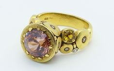 "Pink zircon is exceptionally brilliant, and the beautifully cut carat example in this yellow gold ""Orchard"" series ring makes this a real showpiece. The zircon is a handsome brownish-pink … Gold Texture, Sapphire, Gemstone Rings, Handsome, Fancy, Jewels, Studio, Diamond, Pink"
