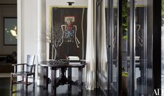 In a corner of the living room, a painting of Ryan by John Mellencamp overlooks an Arts and Crafts table displaying a Pablo Avilla wire sculpture.