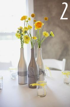 Wedding- DIY Wedding Table decorations. Champagne or wine bottles sprayed with metallic paint, filled with flowers, and tied with ribbon. You can even add a table number to the bottles. Grey and yellow theme shown here. | best stuff