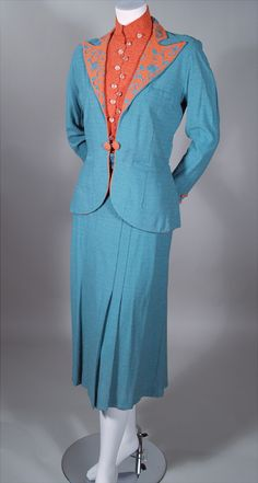 1930s three-piece turquoise and salmon rayon boucle knit Norfolk styled suit. Turquoise fitted jacket: Salmon wide peaked lapels with turquoise swirled motif soutache trim. Three welt pockets. Pleated Norfolk styled back with 1/2 belt. Slim cut skirt: Stitched down pleats front. Box pleat center with a pleat on either side. Salmon novelty knit top: Wide band stand collar. Via RP Vintage.