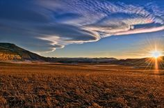 """'Optical and Atmospheric Iridescence' - photo by Michael Menefee (Fort Photo), via Flickr;  a sundown view of the Laramie Foothills north of Fort Collins, CO;  """"Beyond the obvious (real) lens flare across the frame, I had some vibrant iridescence in the clouds to work with. A nice mix of rainbows."""""""