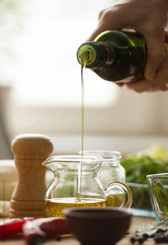 Closeup of female hands cooking vegetables and dressing salad with olive oil in kitchen.