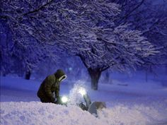 A person clears snow from his driveway after a snowstorm in Urbandale, Iowa.