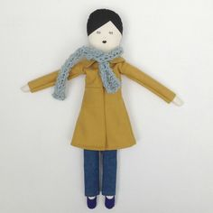 This is Suzy, she is a limited edition doll, she has black hair and a blue and white striped body. She is wearing a warm woolen coat combined with a