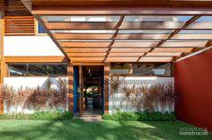 Na entrada social, a porta pivotante imita os brises presentes na fachada. Uma cobertura de madeira com vidro temperado protege o acesso. Projeto do escritório AMZ.