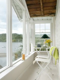 Small white #sunroom with tons of character and a view of the #lake.  What a great spot to relax on the #porch and take in the view.