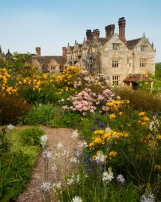 """william robinson Gravetye Manor West SussexRobinson 1890s advocated more natural and less formal-looking plantings of hardy perennials, shrubs, and climbers, and reacted against the High Victorian patterned gardening, which used tropical materials grown in greenhouses. """""""