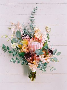 tropical protea wedding bouquet with eculptuys and orchids.