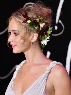 Daily Beauty Buzz: Jennifer Lawrence's Flower Crown | A far cry from the flower crowns dominant at every music festival, Jennifer Lawrence's floral updo was decidedly more elegant, and surprisingly apt for fall.