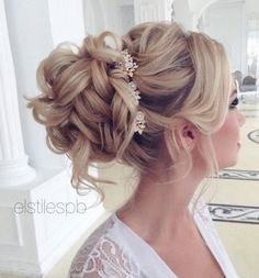 Glamorously sophisticated updo wedding hairstyle with tight curls and white floral hair accessory; Featured Hairstyle: ElStyle