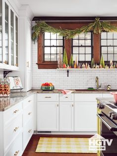 This bright kitchen features white subway wall tile, a yellow buffalo check rug and festive garland. Take a full kitchen tour with HGTV.com.