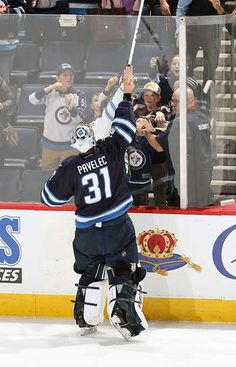 WINNIPEG, MB - JANUARY 18: Goaltender Ondrej Pavelec #31 of the Winnipeg Jets sends a souvenir stick over the glass to lucky fans following a 6-3 victory over the Arizona Coyotes at the MTS Centre on January 18, 2017 in Winnipeg, Manitoba, Canada. (Photo by Jonathan Kozub/NHLI via Getty Images)