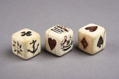 A trio of English nineteenth-century sailors' scrimshaw gambling dice, made from sperm-whale tooth and decorated with such designs as hearts, clubs, spades, crowns, anchors, a compass rose and pseudo-armorials. (Finch & Co)