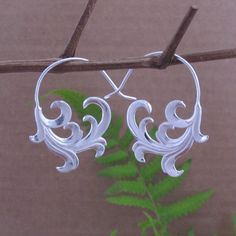 Cast in brass with a polished sterling silver plating, these unique earrings feature an unfurling wave design inspired by the sea. Handcrafted by artisans in Indonesia, these dangle earrings are finished with nickel-free silver plated hook clasps.