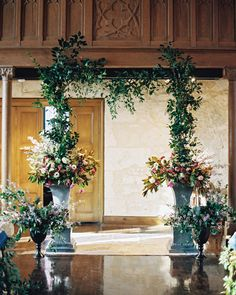 Ceremony backdrop with greenery garland and two sets of potted flowers