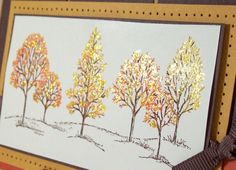 Sponged & inked the grass & tree trunks with choc chip.  Then daubed dusty Durango, more mustard, and ruby red on--ruby red in the center & dusty Durango at the edges. On another tree dusty Durango in the center and more mustard at the edges. Went back & used choc chip marker to make some of the bare branch parts brown & then used gold stickles & dabbed it here & there over the leaf parts