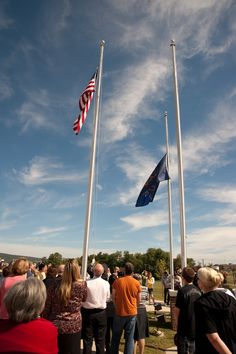 Flags are raised then dropped to half mast.