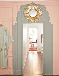 Peindre son couloir via des murs rose pâle et des encadrements de porte gris souris