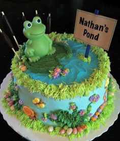 Nathan's Pond baby shower cake - Made for a frog-themed baby shower. Invitation included frogs, caterpillars and snails which are all included in the cake's design. The mother-to-be knows she'll be having a boy who will be named Nathan, hence the sign. The frog on top is a squeaky, bath toy meant as a keepsake. Vanilla buttercream over hazelnut-flavored white cake.