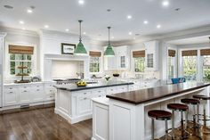 Bright whites throughout this kitchen act in contrast to the dark toned wood countertops and flooring, with large bar seating area on island and unique green chandelier lighting.