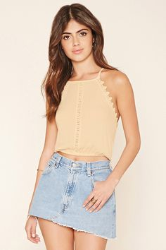 A crinkled woven cropped cami featuring a floral crochet insert at the front, scalloped crochet trim at the bodice, self-tie halter straps forming a keyhole back, and an elasticized hem.