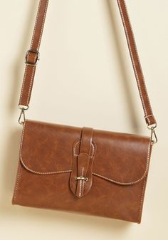 So on and Stow Forth Bag | Mod Retro Vintage Bags | ModCloth.com  Watch yourself while speaking about this brown purse, because its chic design makes it easy to get carried away! This faux-leather satchel's classic silhouette touts white topstitching, a removable strap for clutch conversion, and a matching pouch - all elements you could gush about for days!