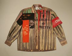"""""""When the 'Dolls' folded Malcolm returned to Vivienne. Her latest design was an anarchy shirt—distressed to look old, with bleached-out stripes, and appliquéd with badges, flags and slogans: 'Only anarchists are Pretty!,' 'Dangerously close to Love,' 'We are not afraid of Ruins,' 'Chaos,' and a woven label from Chinatown of the portrait of Karl Marx, to which Malcolm added a swastika"""
