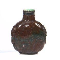 Flacon tabatière en agate mousse rouge à inclusion verte, à décor sculpté de masques de taotie sur les côtés. Bouchon en jadéite.