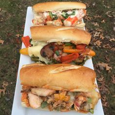 Salmon Cheesesteak with Peppers and a Spicy Mayo (front), Veggie Sandwich (middle), and Seafood Steak (Alaskan King Crab, Lobster, Shrimp) with a Garlic Cheese Sauce (back