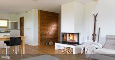 Für behagliche Winterabende ist dieser offene Kamin ideal. Vom Sofa aus kann man die hinter Glas verborgenen Flammen beobachten und die Wärme genießen. Die Holzverkleidung der Wand verleiht dem Wohnzimmer eine rustikale Note. Der offene Wohnbereich vereint Küche, Essbereich und Wohnecke in einem.