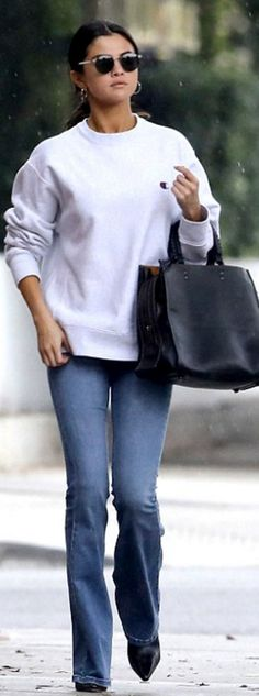 Who made  Selena Gomez's white sweatshirt and black handbag?