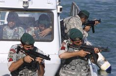 Iranian navy members take positions during a drill in the Sea of Oman, Wednesday, Dec. 28, 2011. Iran's navy chief warned Wednesday that his country can easily close the strategic Strait of Hormuz at the mouth of the Persian Gulf, the passageway through which a sixth of the world's oil flows. The navy is in the midst of a 10-day drill in international waters near the strategic oil route.