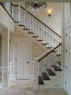 iron balusters - plus, smaller newell posts with larger newell at entrance plus like the trim on walls and around stairs: