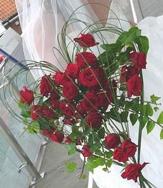 Hvite roser! Ikke eføy. Kanskje hjerte med tynn sølvtråd i stedet for gress? Perleheng fra spissen på hjertet med hvite og blå perler?
