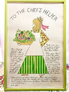 Vintage Art Kitchen Dining Room 1960s. Chefs Helper Hand-Drawn Graphics in Lime-Green Frame. Adorable!  This charming retro framed kitchen art features a chefs helper girl/woman in green-striped flair pants, apron, and flower-power blouse holding a sumptuous bowl spilling over with vegetables, bread, and greens. Wooden frame is painted lime green; art is covered by intact glass; original framing paper remains on reverse; hanging hook is attached; original identification sticker reads: ha...