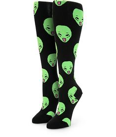 """Get a far out look with these long length thigh high socks made with a stretchy and breathable knit construction covered in an alien face print with small """"We Out Here"""" text at the cuffs."""