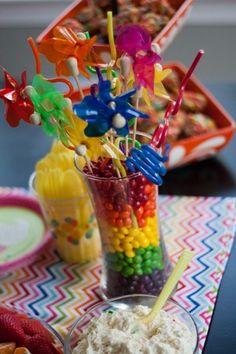 Dollar Store pinwheels + Dollar Store vases + skittles = rainbow centerpieces!