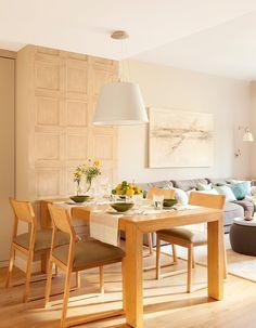 Comedor junto al salón con mobiliario de madera y vajilla en verde