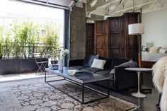 A garage door opens to a balcony and fills the loft with light. An antique wooden screen divides the bedroom from the living room. Joan McNamara LA loft photographed by ljoliet Loft Interior, Interior Design, Interior Doors, Loft House, Step Inside, Industrial Chic, Minimalist Home, Minimalist Apartment, Oeuvre D'art