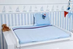"""Bezaubernde Wickelauflage aus der Kollektion """"Anker"""" von KRS-Design. Der blau-weiß gestreifte Stoff und die Borten in rot-blau unterstreichen den maritimen Stil. Der gestickte Anker auf dem oberen Teil der Wickelauflage ist jedoch der absolute Blickfang im Kinderzimmer."""