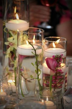 Pink & green flowers submerged in vase trio with floating candles
