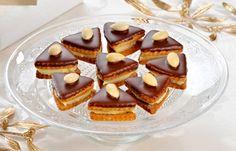 V troubě upečené různé tvary vánočního cukroví, slepené spolu po dvou mandlovým krémem, ozdobené čokoládovou polevou a půlkou mandle.