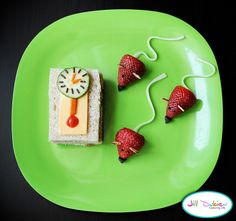 from meet the dubiens      clock - ham and cheese sandwich cut into rectangle, cheese slice on top with a carrot and cherry tomato pendulum. The clock face is a sliced cucumber with spinkles and carrot arms.    mice - strawberries with cheesestring tails, slivered almond ears, sprinkle eyes, and chocolate chip noses.