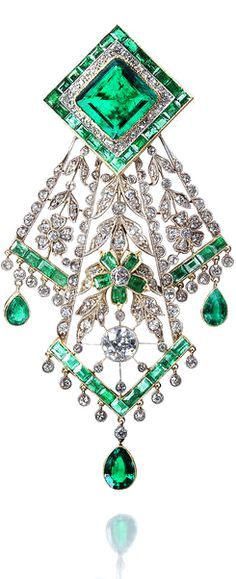 An emerald and diamond handkerchief brooch, circa 1910 The lozenge-shaped surmount set with a step-cut emerald, within borders of old brilliant and single-cut diamonds and calibré-cut emeralds, suspending an openwork floral and foliate pendant designed to resemble folded lace, millegrain-set throughout with similarly cut diamonds and emeralds, terminating in a fringe of pear-shaped emerald and single-cut diamond drops, mounted in platinum and yellow gold.