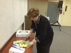 Professor Valerie Andrews cuts king cake for her PR Capstone class.