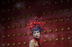 A woman wearing a dress and a headgear inspired by traditional Chinese costume poses for pictures in Lijiang, Yunnan province