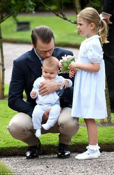 Prince Daniel planted a tender kiss on his son's head as Princess Estelle looked on ...