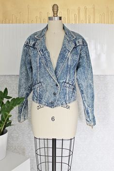 Vintage 1980's jean jacket. All done in an iconic, acid wash denim accented with suede. Snap-button closures with two pockets. Both the sleeves and the back of the jacket are detailed with lace-up sue